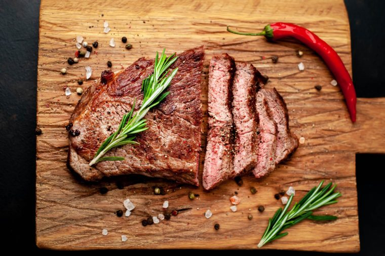 Ready to eat New York black angus steak with ingredients on a cutting board. Ready meal for dinner on a dark stone background.