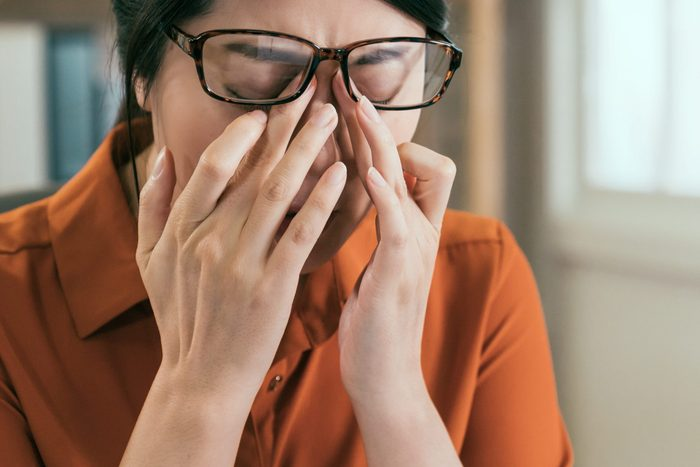 stressed asian female architect having headache working in office. young girl engineer in glasses rubbing eyes painful sick tired exhausted hardworking. overwork interior designer massage nose bridge