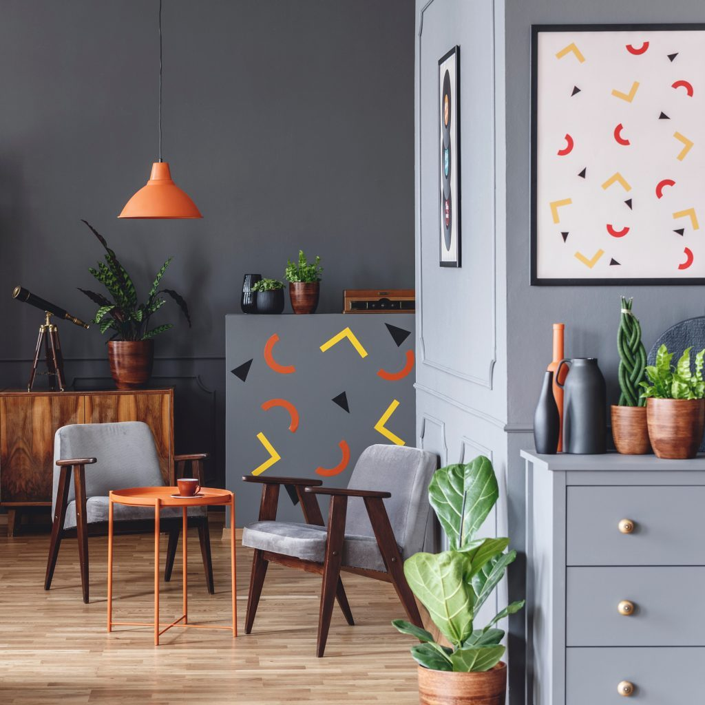 Geometric poster in spacious grey flat interior with orange lamp above table and armchair