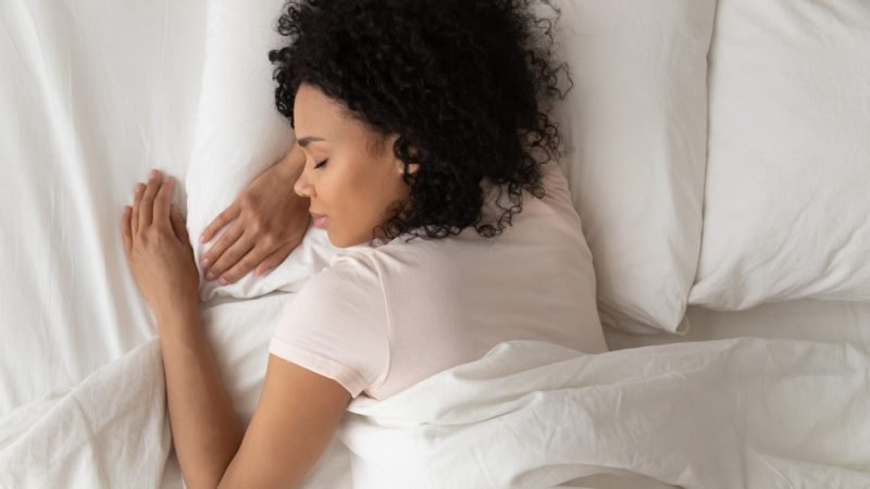 Healthy serene young african american girl sleeping well in comfortable cozy fresh bed on soft pillow white linen orthopedic mattress, calm sleepy black woman enjoy peaceful sleep at home, top view