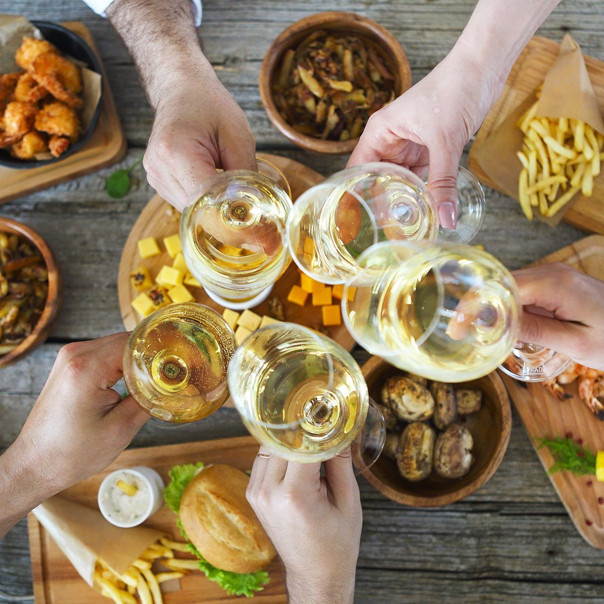 Hands with white wine toasting over served table with food.