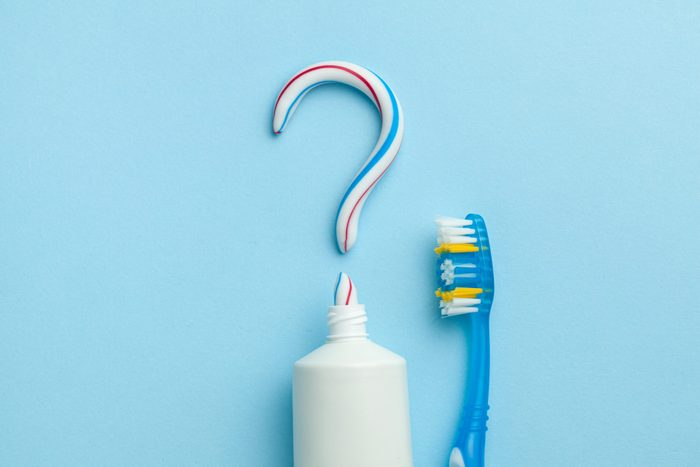 Question mark from toothpaste. The concept of choosing good toothpaste for teeth whitening. Tube of colored toothpaste and  toothbrush on blue background.