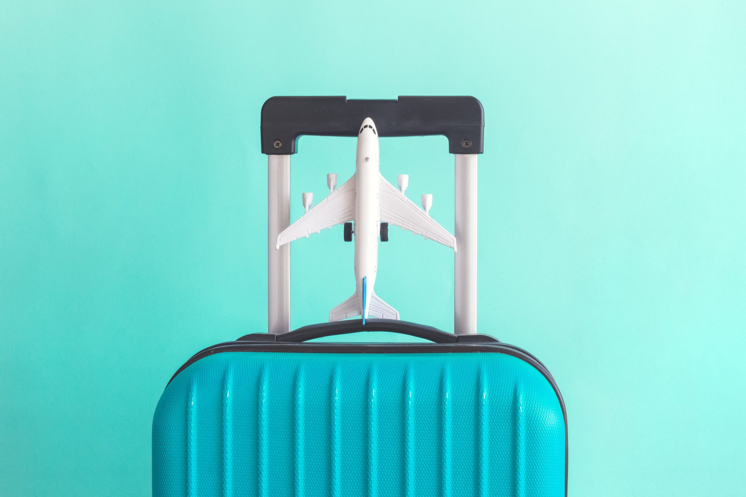 Suitcase and airplane model on pastel green background minimal creative travel concept