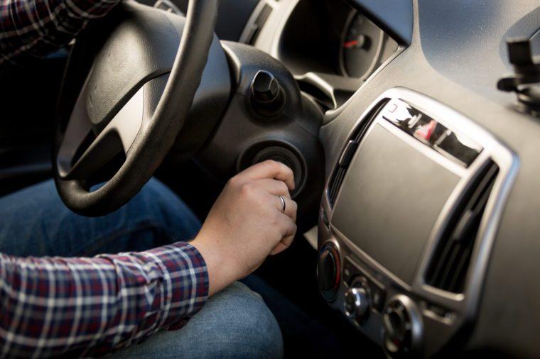 Closeup shot of man inserting key in car ignition lock