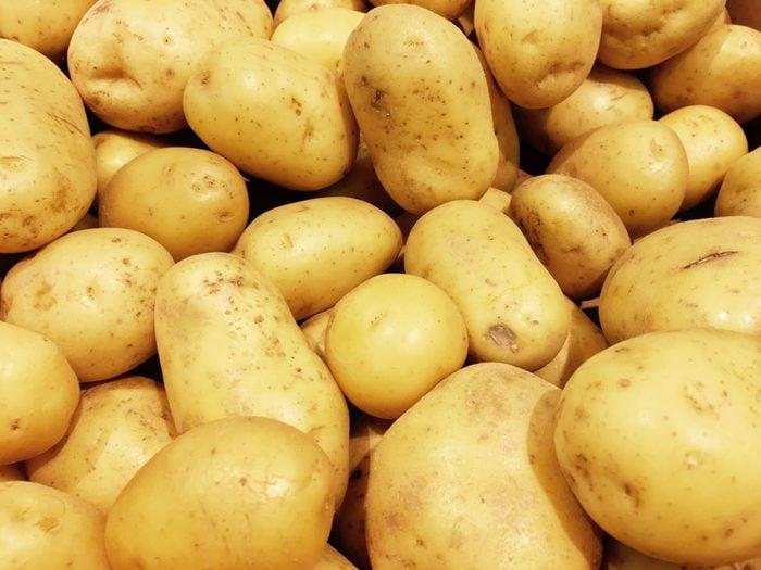 Fresh organic potato stand out among many large background potatos in the market. Heap of potatos root. Close-up potatos texture. Macro potato.