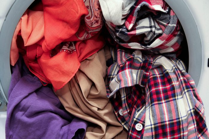 Front loading washing machine overloaded with colorful dirty clothes, close up view