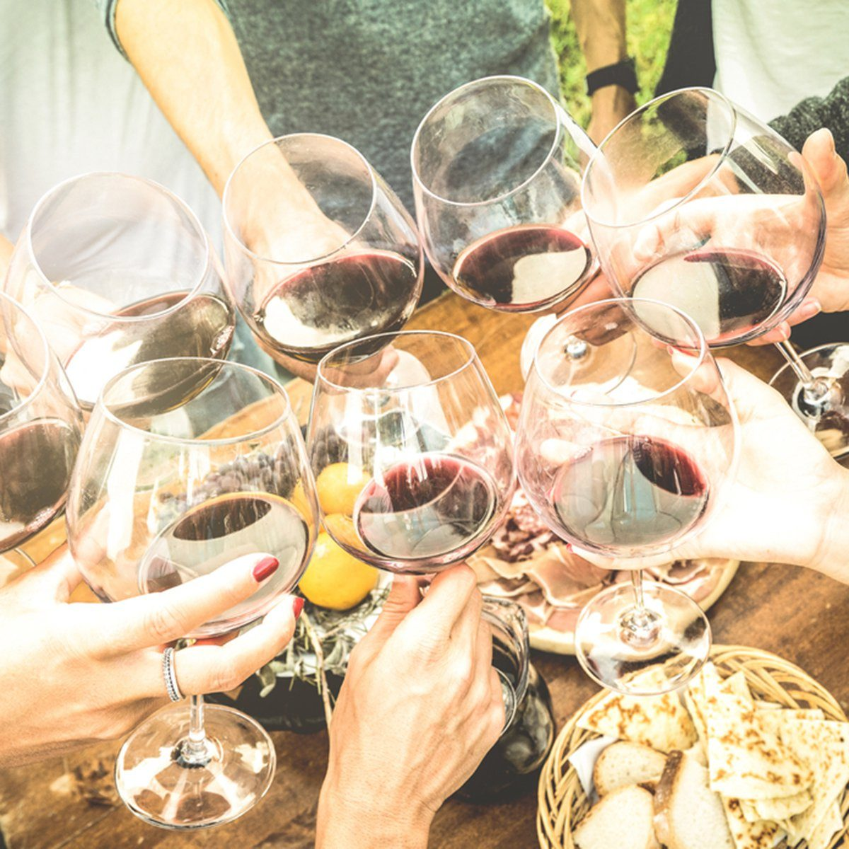 Friends hands toasting red wine glass and having fun outdoors cheering with winetasting - Young people enjoying harvest time together at farmhouse vineyard countryside - Youth and friendship concept; Shutterstock ID 570070135