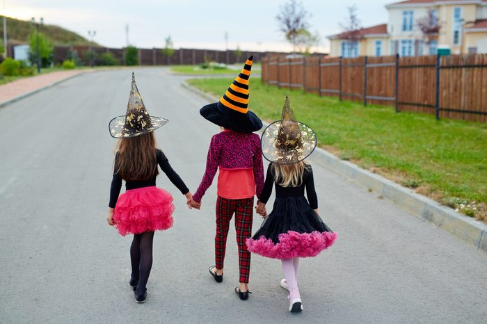 Rear view of little witches holding by hands while walking down road