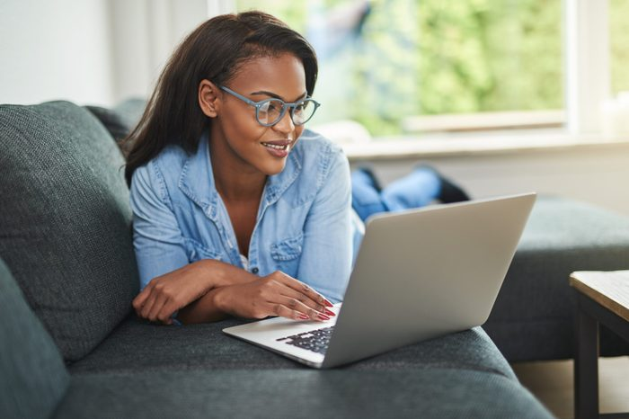 Smiling young African woman lying down on her living room sofa using a laptop to browse the internet