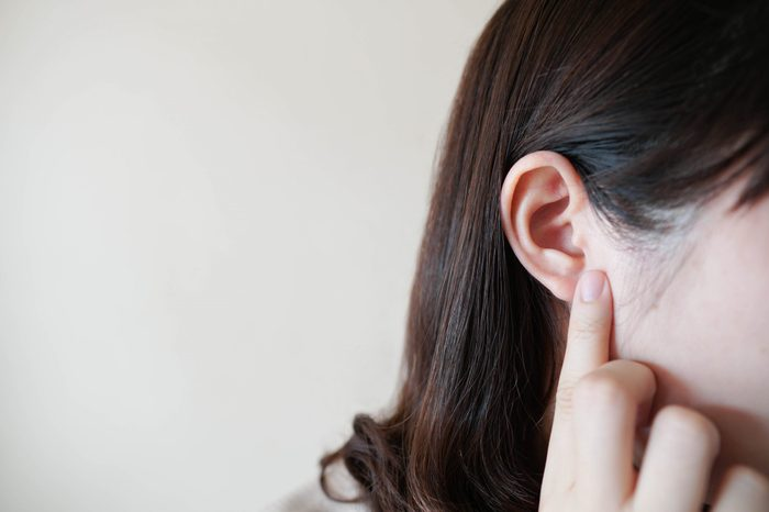 Young woman pointing finger to her ear over white background with copy space. Concept of hearing, listening, ear disease or otoplasty plastic surgery. Close up.