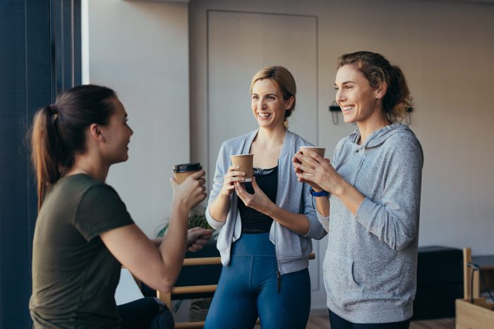 Women relaxing after workout holding coffee and talking in a pilates gym.