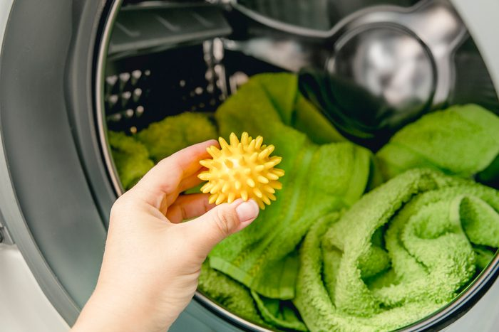 Hand holding yellow dryer ball in front of dryer machine filled with green towels