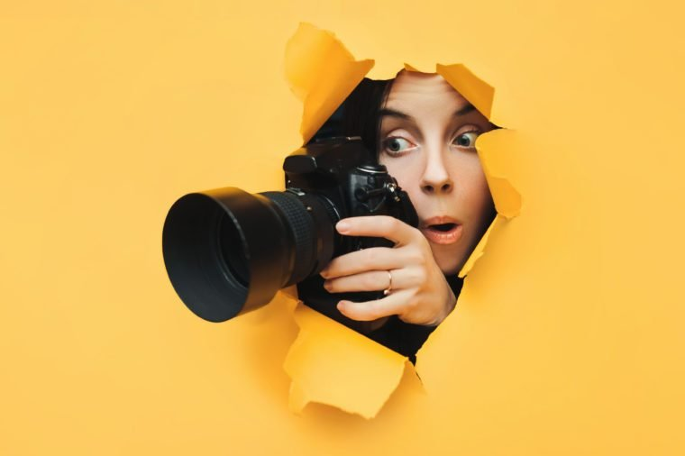 A paparazzi funny girl with a camera looks out from cover and looks at what is happening with her mouth open. Yellow paper, torn hole. Tabloid press. In search of the plot for photo stocks.
