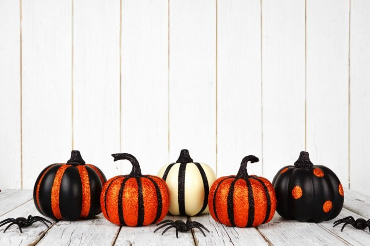 Black and orange glittery Halloween pumpkins against a white wood background