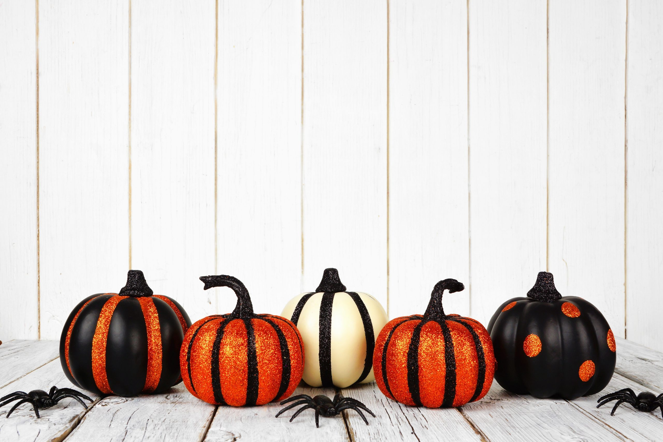 Black and orange glittery Halloween pumpkins against a white wood background