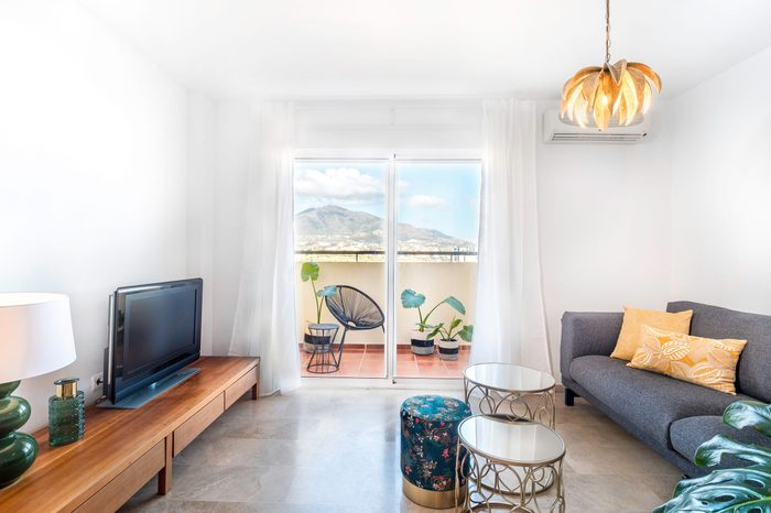 Bright living room with sofa, wooden table, side tables, tv,plants and big window to a terrace with mountain view. Summer holidays vacation.Spacious modern interior