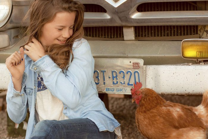 a girl, smiling, recoils from the chicken next to her