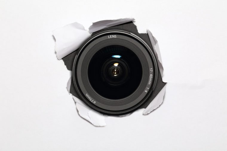 Camera lens hiding behind the paper wall, ready to take a snapsho
