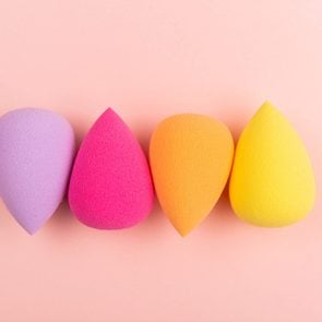 Colorful beauty sponges on pink background. Makeup tool for applying and blending products such as foundation, concealer. Horizontal shot. Copy space for text.