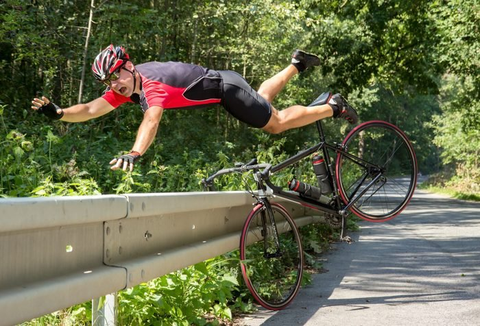 Cyclist falls off the bike into bushes. Accident on the road. Biker fall from the bike into the grass. Bicycle accident when falling through road barriers. Accident man in sports.