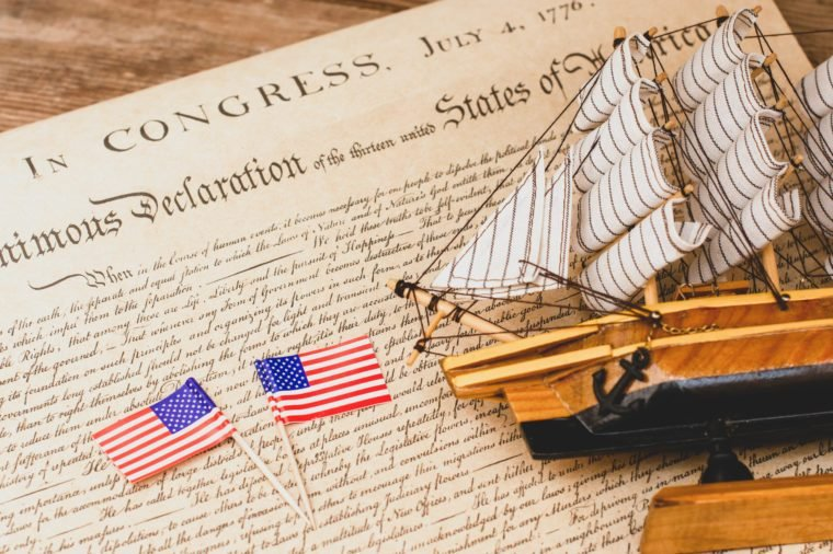 American flag and ship made of wood and fabric handmade on the background of an excerpt from a copy of the document of 1776 on the signing of American independence
