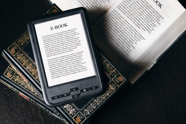 E-book reader device on desk in library. Alternative for traditional books