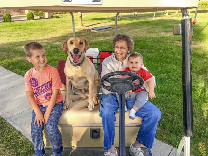grandmother with two grandkids and a dog sit in a golf cart