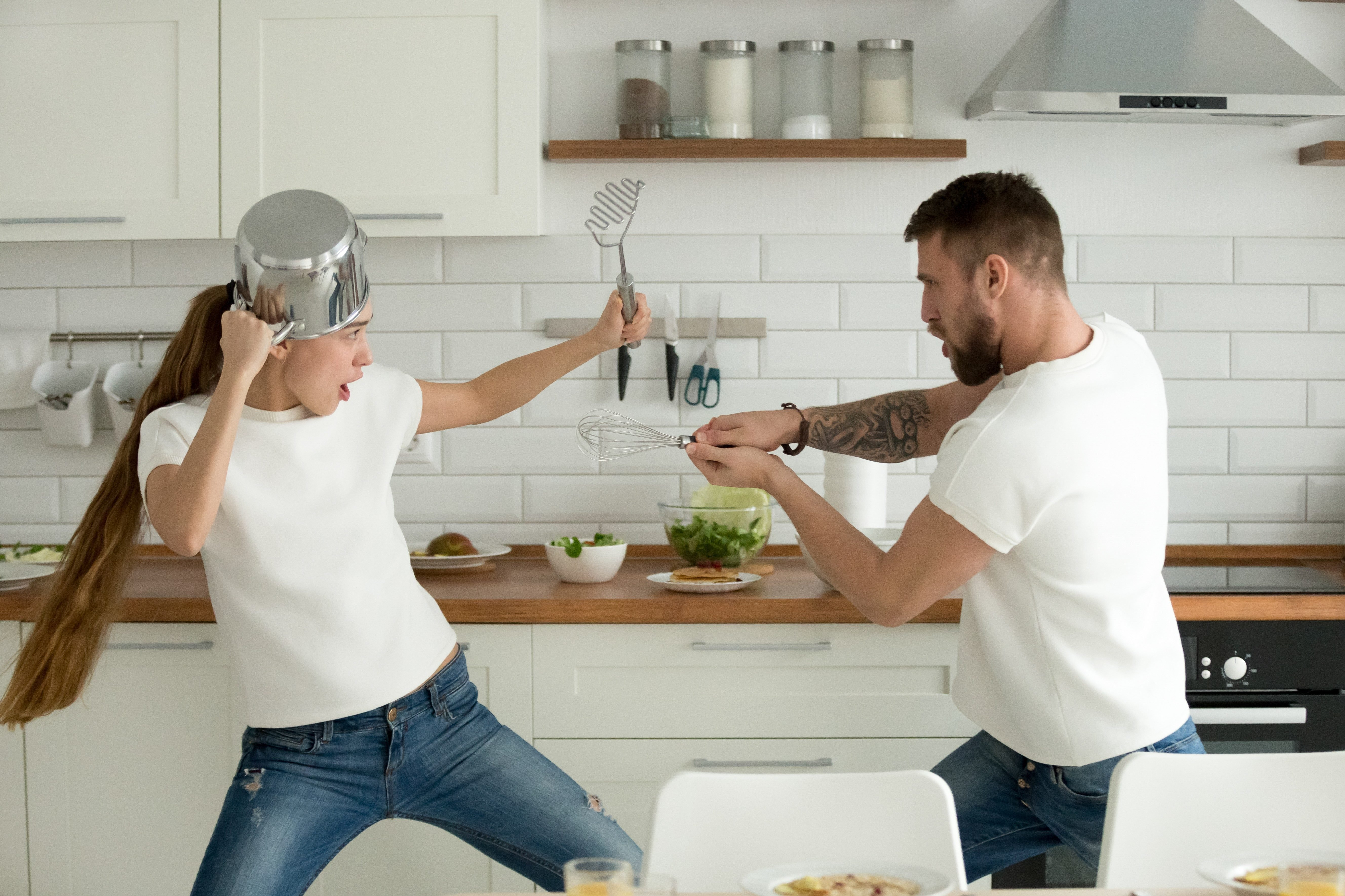 Funny couple pretending fight with utensils tools while cooking at home together, husband and wife having fun feeling playful holding kitchenware struggling in the kitchen preparing healthy food