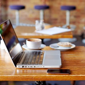 a laptop, a smartphone, a coffee, and a pastry sit on a table at a cafe with free open wifi