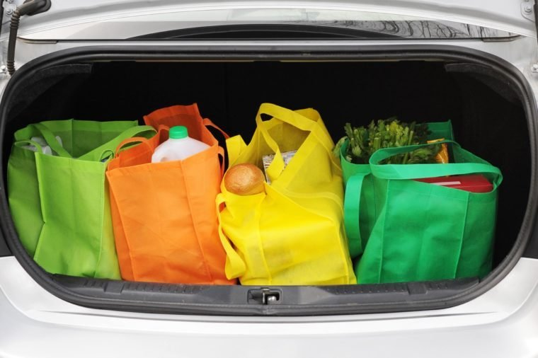 reusable bags with groceries in a car trunk