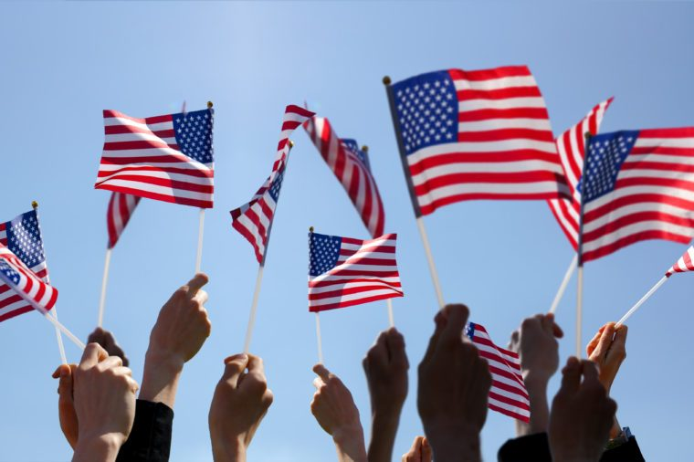 Group of People Waving American Flags over blue sky