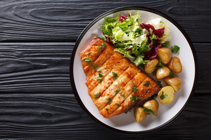 Healthy lunch grilled swordfish fillet with fried potatoes and fresh salad close-up on a plate on a wooden table. horizontal top view from above