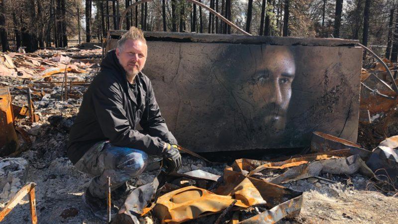 Shane Grammer stands next to spray paint art portrait