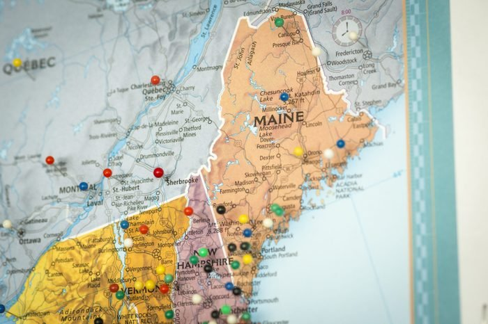 Colorful detail map macro close up with push pins marking locations throughout the United States of America Maine ME