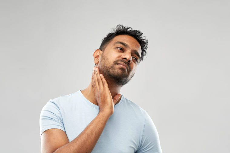 health problem and people concept - unhealthy indian man suffering from sore glands or tonsils over grey background