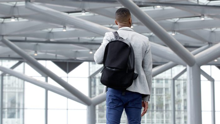 Rear view portrait of a young man standing in empty airport
