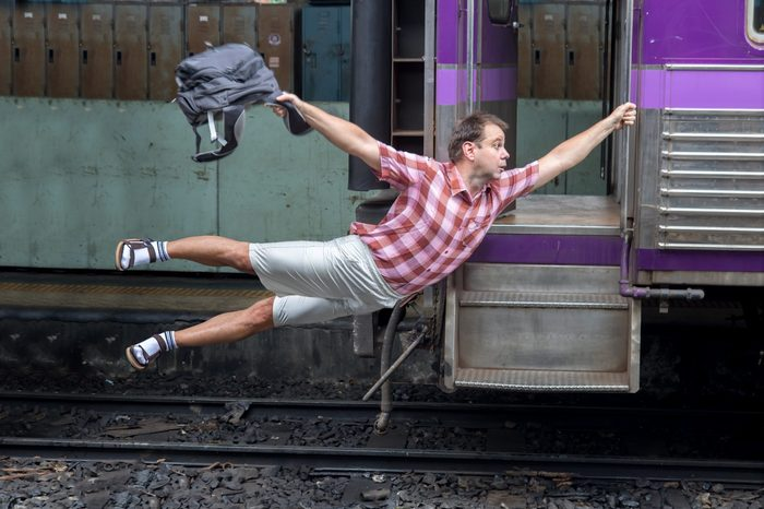 Man with backpack flies behind a moving train. Tourist holding a moving train from a railway station. Funny traveler catches the train in motion.Journey to the last minute.