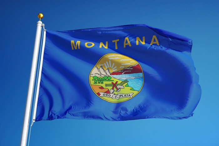 Montana (U.S. state) flag waving against clear blue sky, close up, isolated with clipping path mask alpha channel transparency, perfect for film, news, composition