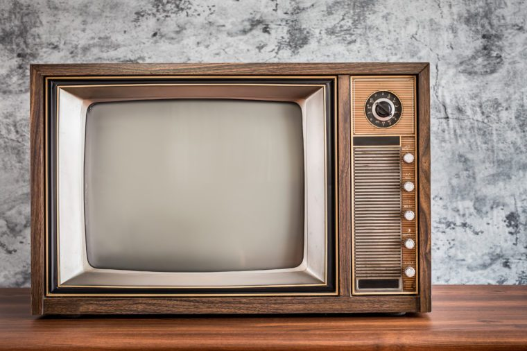 Old television on wooden table with concrete wall background, classic retro TV with copy space on the right