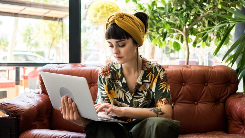 Pretty brunette girl checks her mail on small portable laptop while waiting her order in cafe shop. She travels during her summer vacations and sometimes works remotely