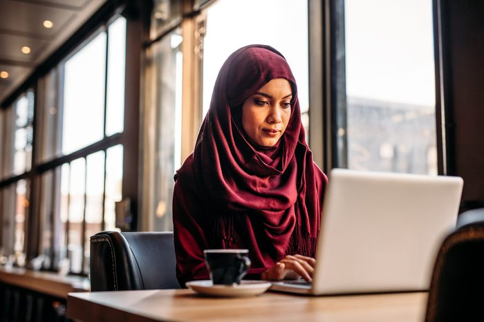 Pretty islamic female sitting at cafe table and working on laptop with coffee in side. Businesswoman in hijab working from a coffee shop.