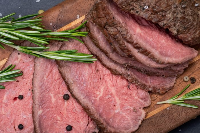 Sliced Grass Fed juicy Corn Roast Beef garnished with Fresh Rosemary Herb and Rainbow Peppercorns on natural wood cutting board.