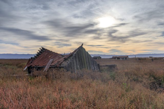 Sunset over abandoned house at Drawbridge, the last remaining ghost town in San Francisco Bay Area. Don Edwards San Francisco Bay National Wildlife Refuge, Fremont, Alameda County, California, USA.