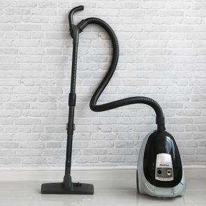 Vacuum cleaner on white concrete background in the house.