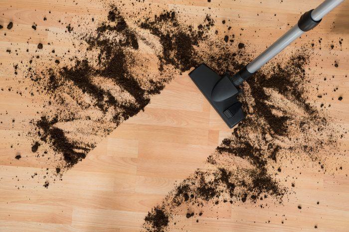 Vacuum cleaning hardwood floor in living room