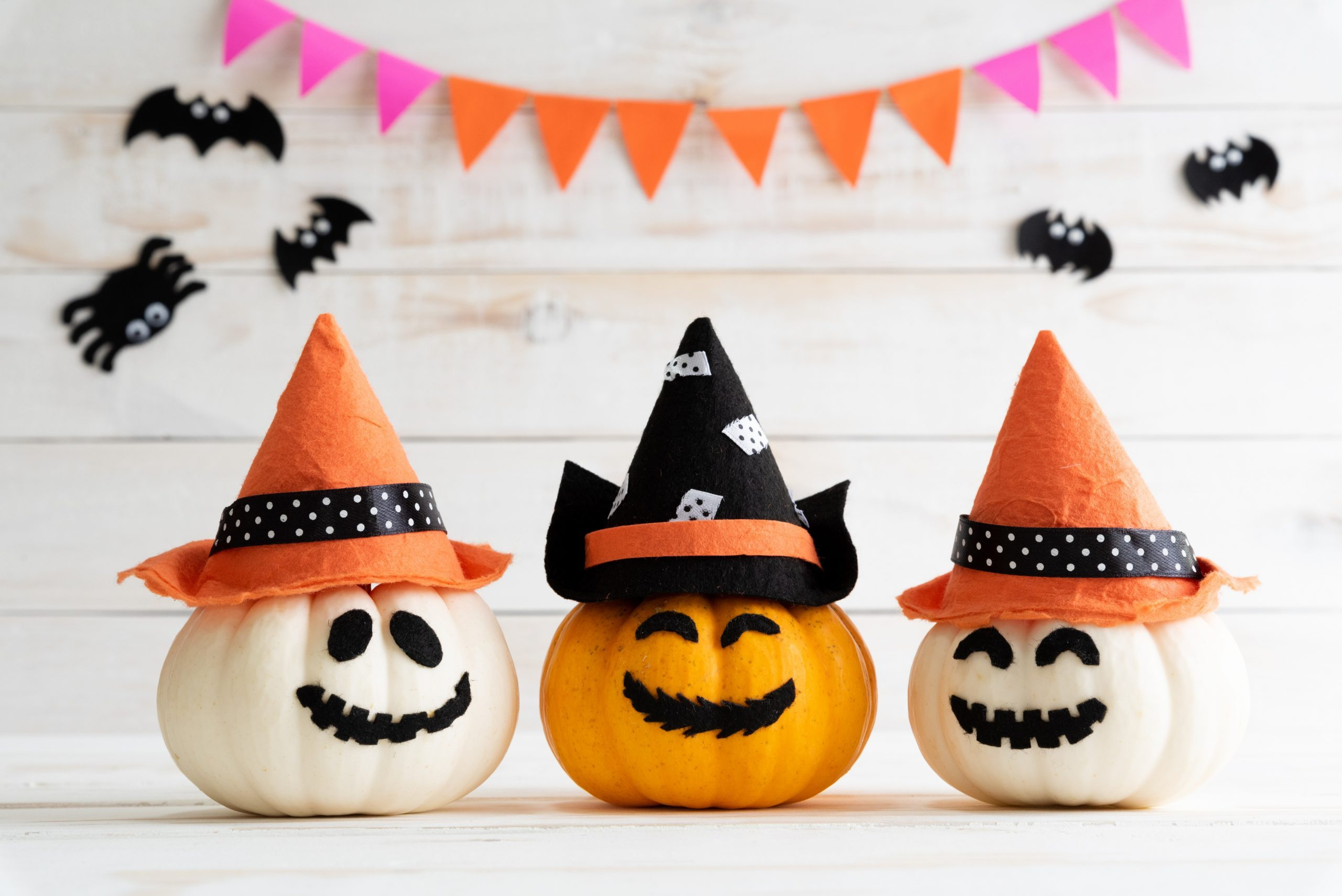 White and yellow ghost pumpkins with witch hat on white wooden borad background with bat. halloween concept.