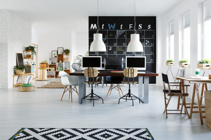 White office interior with desk, computers, chair and pattern rug