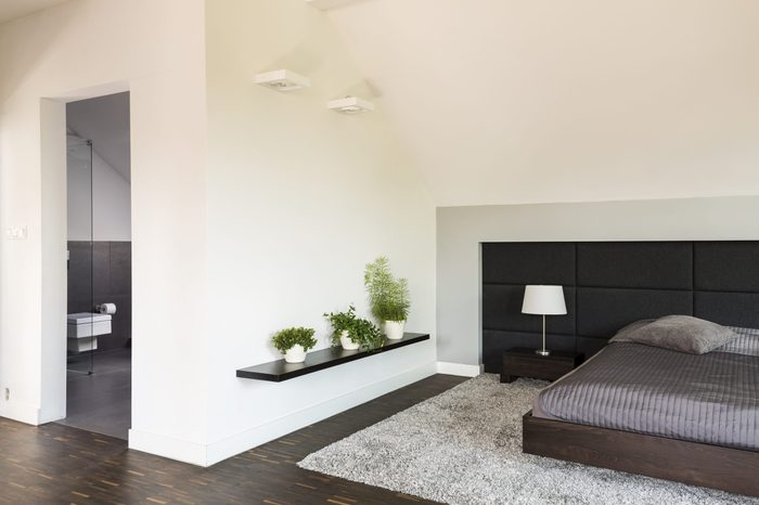 Shot of a spacious modern bedroom connected to a bathroom
