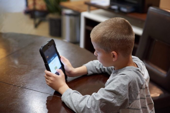 Boy using tablet indoors to learn.