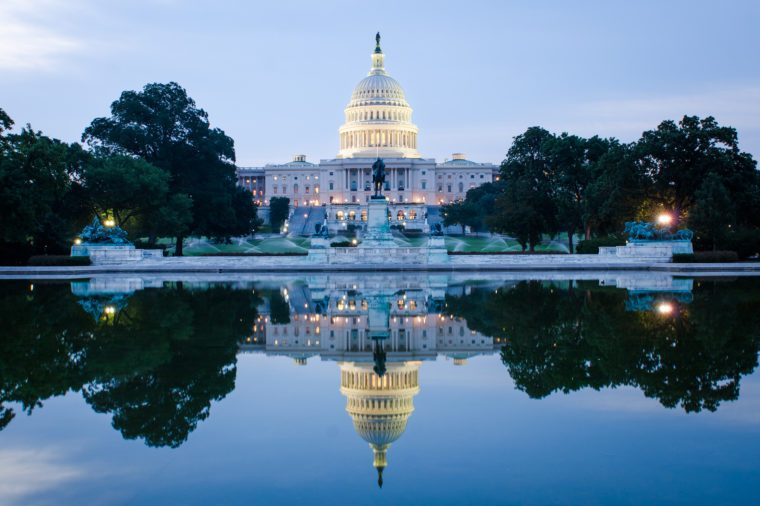 Washington DC, US Capitol Building in a cloudy sunrise with mirror reflection